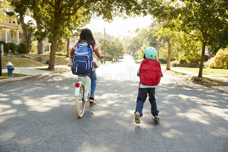 Sister With Brother Riding Scooter And Bike To School stock images