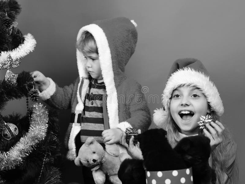 Sister and brother siblings decorate Christmas tree. Kids with happy faces unpack present boxes on red background. Girl and boy in xmas hat and hood play with stock images