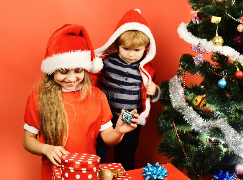 Sister and brother siblings hold toys for Christmas tree. Girl and boy in xmas hats hold tree decorations. Kids with happy faces play with xmas balls on red stock image