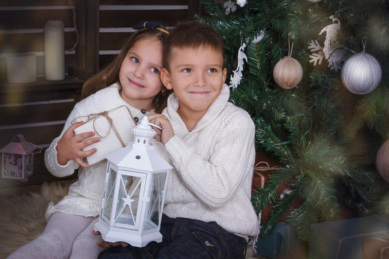 Sister and brother sitting under Christmas tree with gifts stock photo