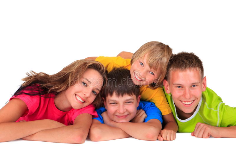 Sister and brothers having fun. Colorful portrait of three happy smiling brothers and their sister lying prone on a white background stock photo