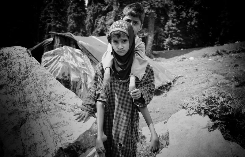 Sister carrying brother everyday for playing on mountains. A 9-year-old nomad girl carrying her physically challenged brother on her back outside their royalty free stock photo