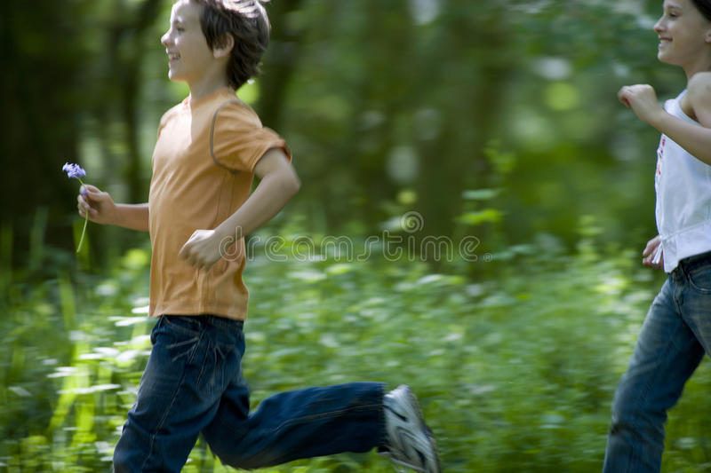 Sister (7-9) chasing brother (8-10) outdoors, side view royalty free stock image