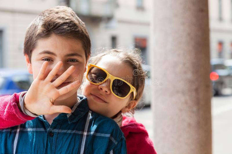 Child covers his mouth of her brother, portrait stock image