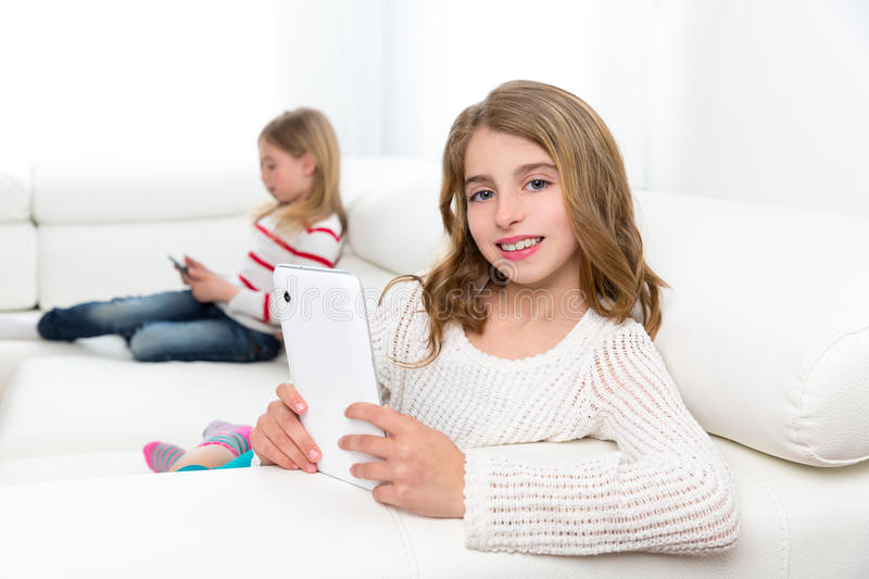 Sister friends kid girls playing with tablet pc in sofa. Children sister friends kid girls playing with tablet pc on white sofa royalty free stock photos
