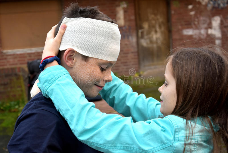 Sister gives first aid. To her brother she bandaged his head after an accident stock photography