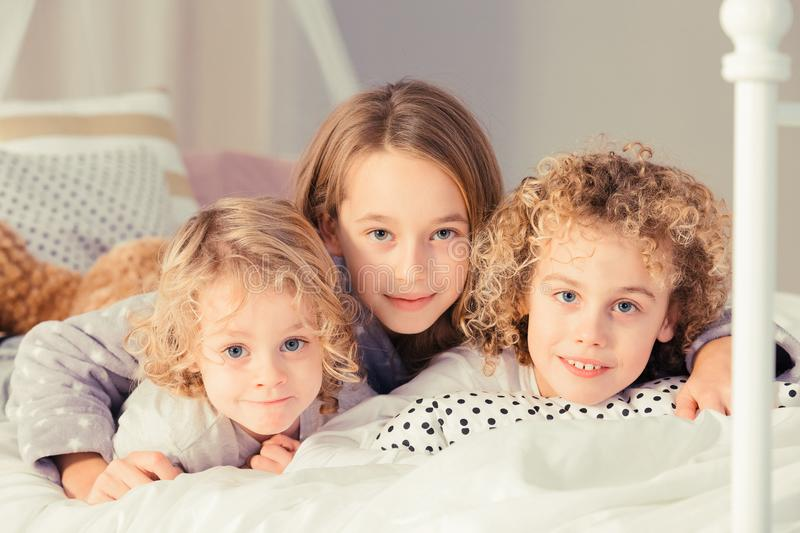 Sister hugging brothers. Sister hugging her two little brothers on the bed royalty free stock image