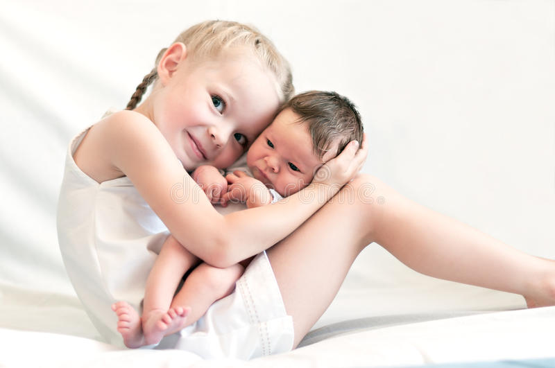 Sister hugs her younger brother. 5 years old sister hugs her younger 2 weeks old brother royalty free stock photos