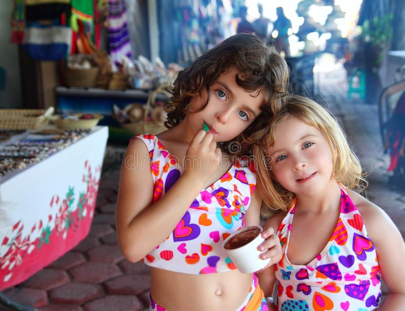 Sister little girls eating chocolate ice cream. Beautiful sisters little girls eating chocolate ice cream in mexican market royalty free stock photos