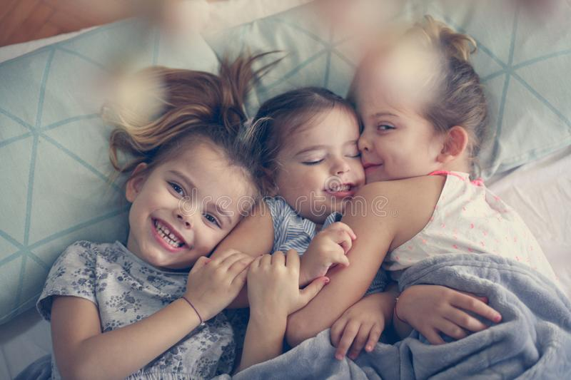 Sister love. From above. Three little girls lying in bed and playing. Space for copy stock photo