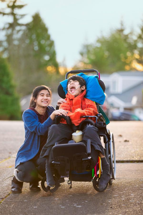 Sister next to disabled little brother in wheelchair outdoors royalty free stock photo
