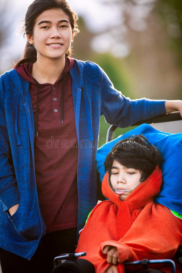 Sister next to disabled little brother in wheelchair outdoors stock photos