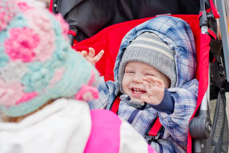 Sister plays with her baby brother in a stroller. On a walk stock photos