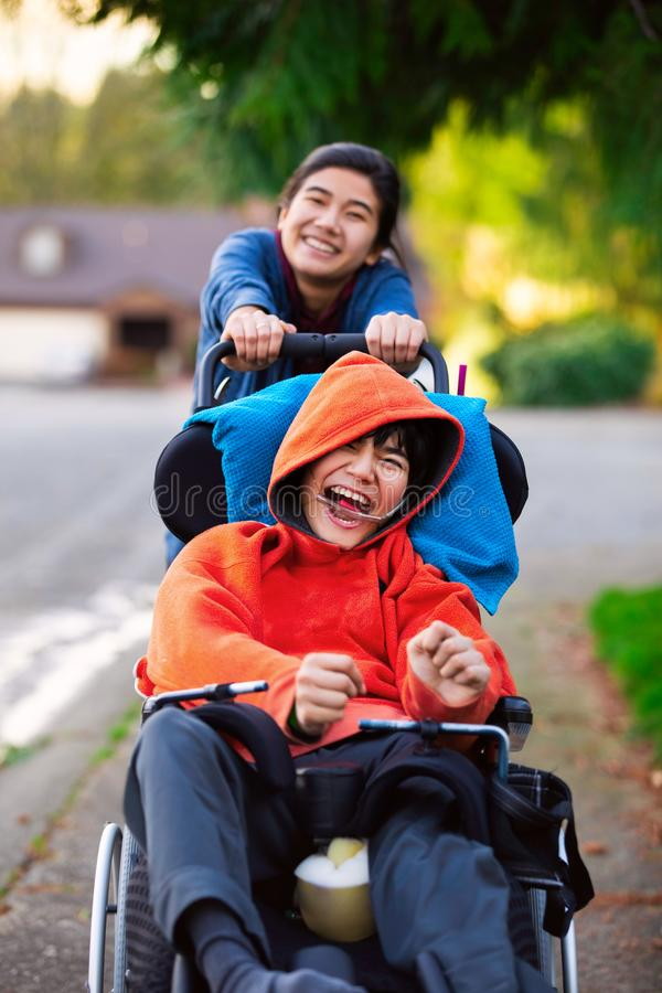Sister pushing disabled little brother in wheelchair around neighborhood stock image