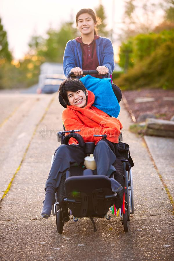 Sister pushing disabled little brother in wheelchair around neighborhood royalty free stock photography