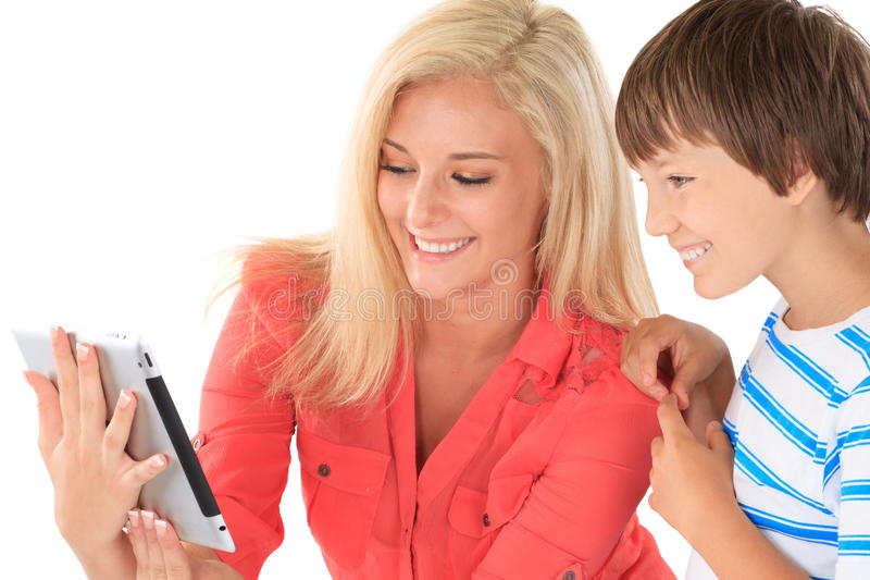 Sister showing brother tablet. Happy sister in pink blouse showing electronic tablet or e-book to brother wearing blue striped t-shirt on white background stock images