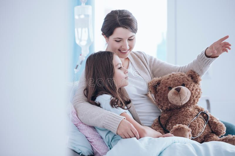 Sister taking care of child. Older sister taking care of a sick child lying in a hospital bed with teddy bear stock images