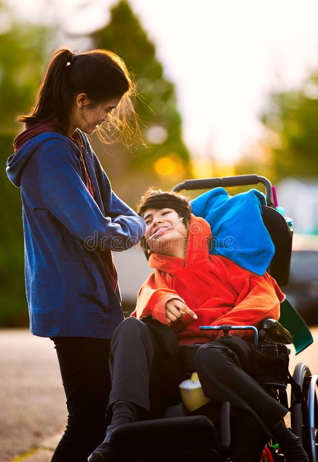 Sister talking to disabled little brother in wheelchair outdoors royalty free stock images