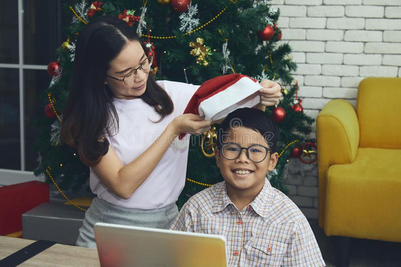 Sister wear the Santa hat to younger brother who smiling. Christmas and New year celebration concept stock images