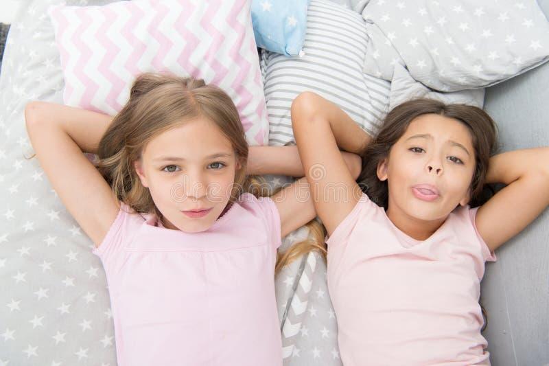 Sisterhood concept. Sharing secrets. Kids relaxing on bed. Sisters preparing sleep. Nice evening. Best friends. Children royalty free stock photography