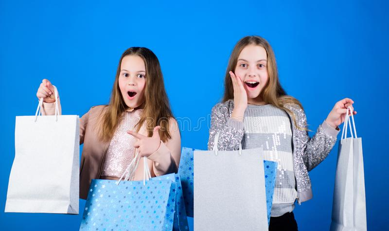 Sisterhood and family. savings on purchases. Happy children. Little girl sisters. Sales and discounts. Kid fashion. Blue. Background. Small girls with shopping royalty free stock photography