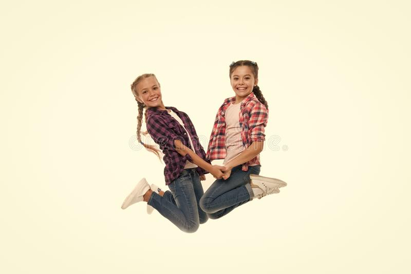 Sisterhood goals. Sisters together isolated white background. Sisterly relationship. Sisterhood is unconditional love. Girls playful sisters having fun jumping stock images