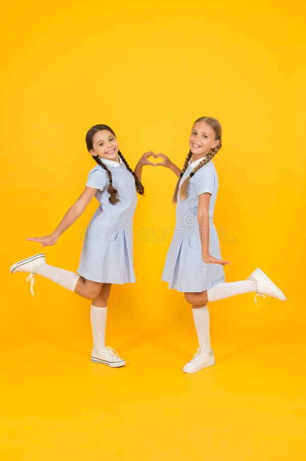 Sisterhood love. children in vintage style. old school. happy friends on yellow background. kid fashion. childhood. Happiness. small girl in school uniform with stock photography