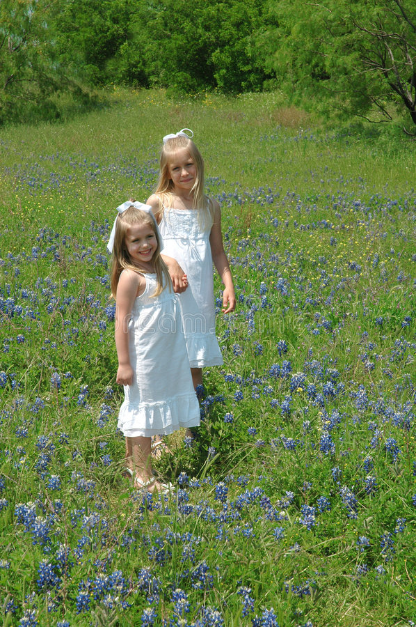 Sisters. Two sister spending the day in blue bonnet flowers Blue Bonnets are native Texas flowers. The Blue Bonnet is the State Flower of Texas, USA stock photos