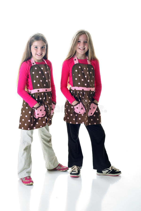 Sisters in aprons. Shot of sisters in aprons on white stock photography