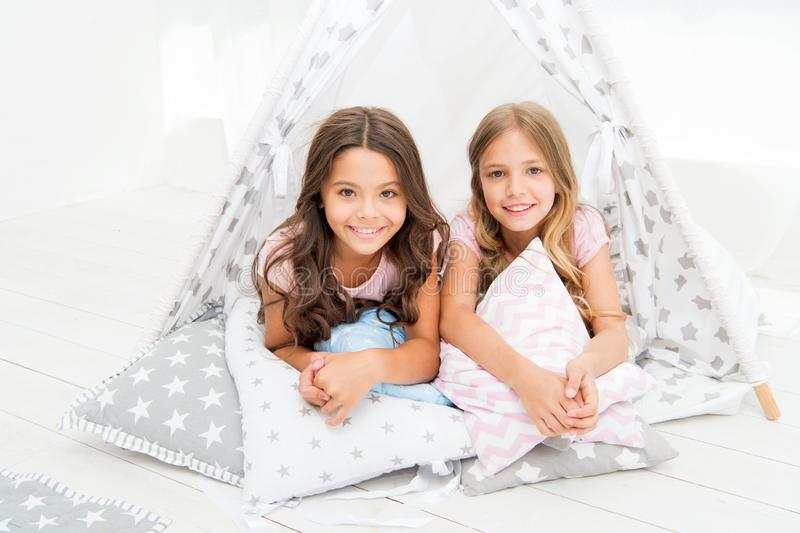 Sisters or best friends spend time together lay in tipi house. Girls having fun tipi house. Girlish leisure. Sisters royalty free stock photo