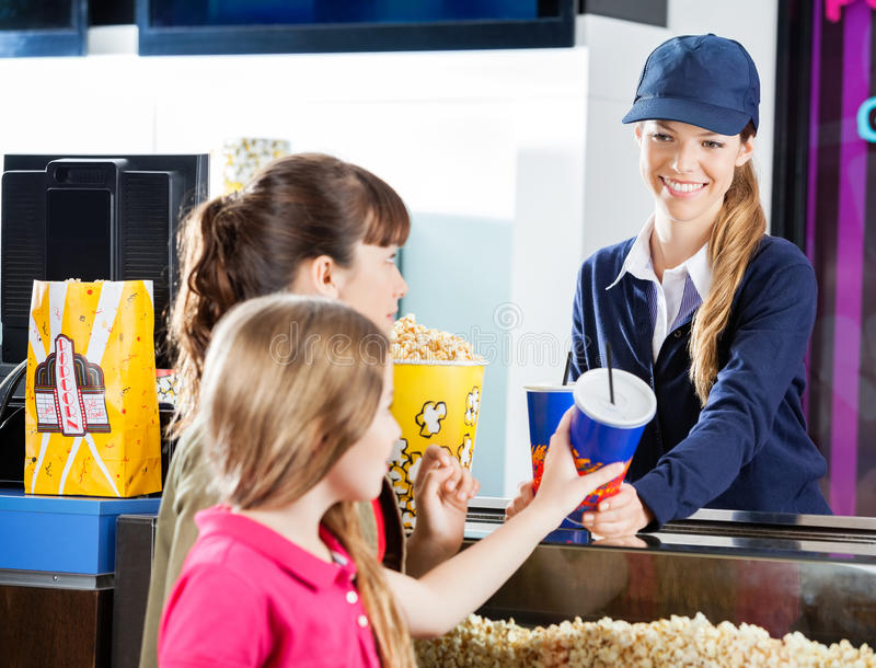 Sisters Buying Snacks From Concession Worker At. Sisters buying snacks from female concession worker at cinema counter stock photo