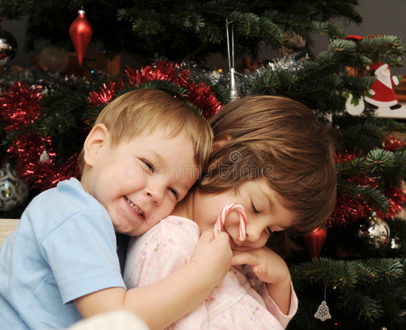 Sisters at Christmas. A portrait of two sisters hugging next to a Christmas tree royalty free stock image