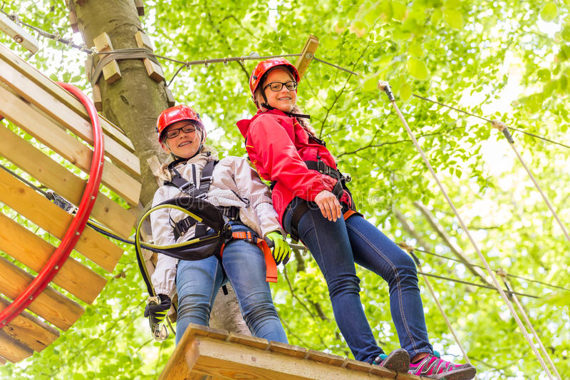 Sisters climbing in high rope course together stock images