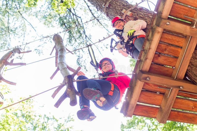 Sisters climbing in high rope course together royalty free stock photo