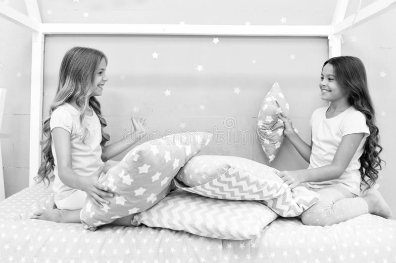 Sisters communication. Children relax and having fun in evening. Sisters leisure. Girls in cute pajamas spend time. Together in bedroom. Sisters communicate royalty free stock images