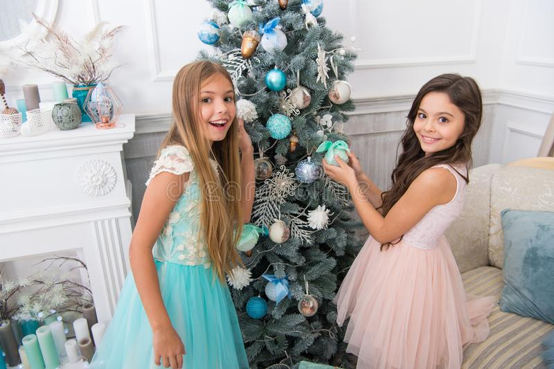 Sisters decorating tree. Cherished holiday activity. Kids fashionable dresses decorating christmas tree. Family royalty free stock photos