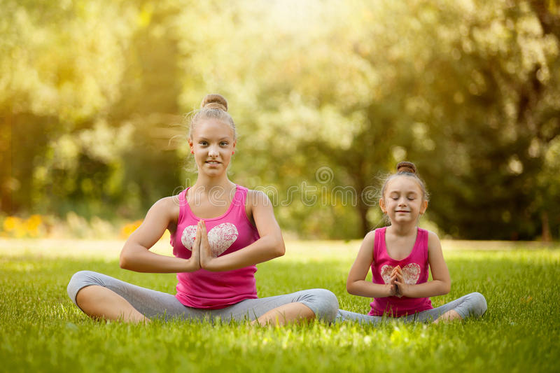 Sisters doing exercise outdoors. Healthy lifestyle royalty free stock image