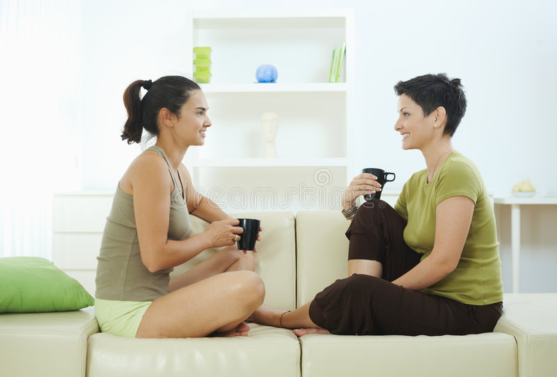 Sisters drinking coffee on couch royalty free stock photos