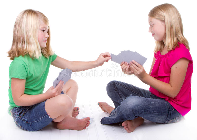 Sisters or friends playing cards stock images