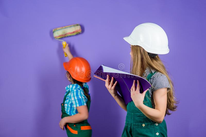 Sisters happy renovating home. Home improvement activities. Renovation team. Kids girls planning renovation. Repaint. Walls. Move in new apartment. Children stock image