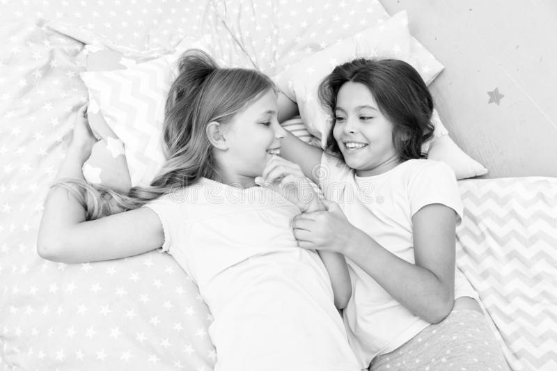 Sisters happy small kids relaxing in bedroom. Friendship of small girls. Leisure and fun. Having fun with best friend. Children playful cheerful mood having royalty free stock photos