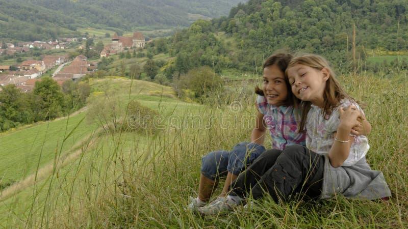 Sisters on hillside, Copsa Mare, Transylvania, Romania stock images