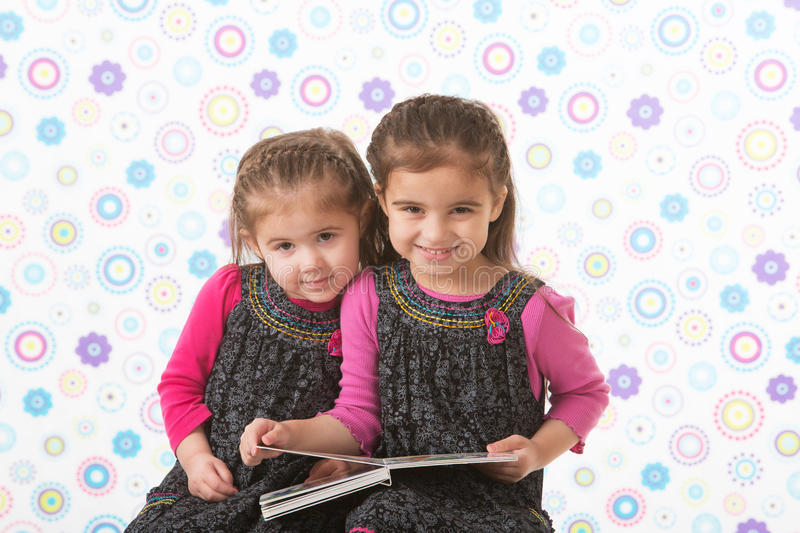 Sisters holding book royalty free stock images