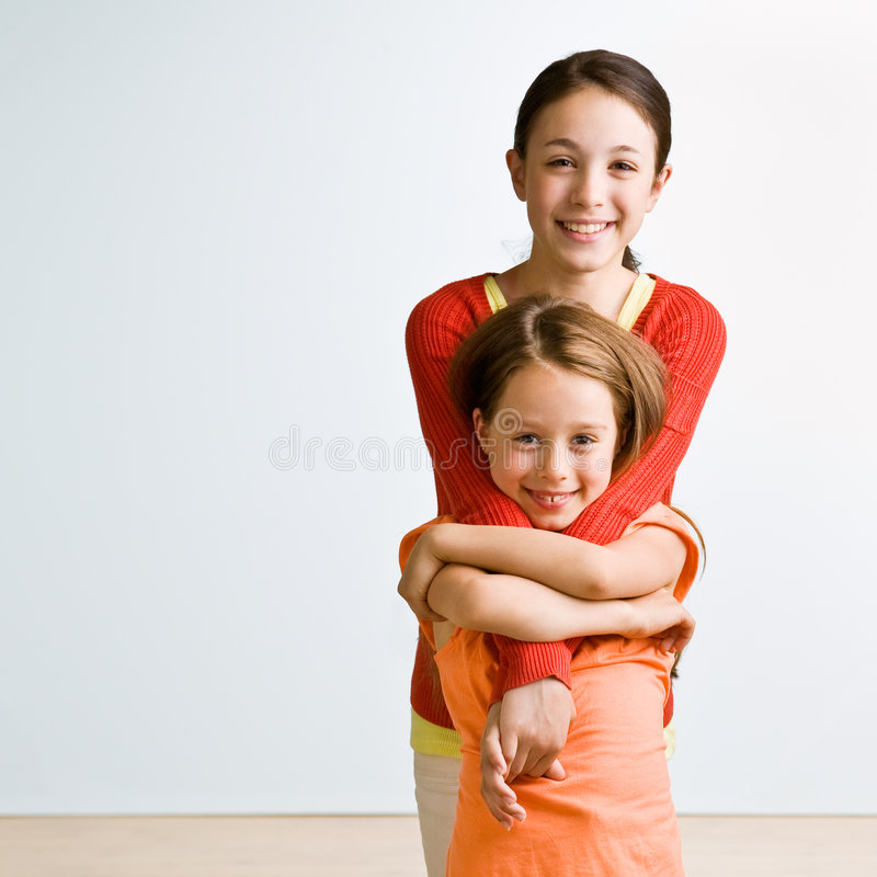 Sisters hugging stock photo