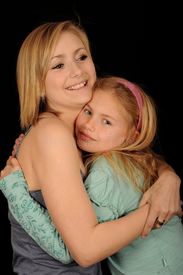Sisters hugging. A portrait of two cute sisters hugging each other, on black studio background stock photo