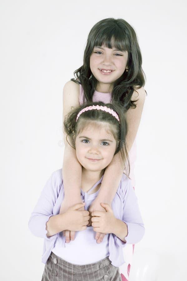 Sisters huging. Two little girls huging stock photos