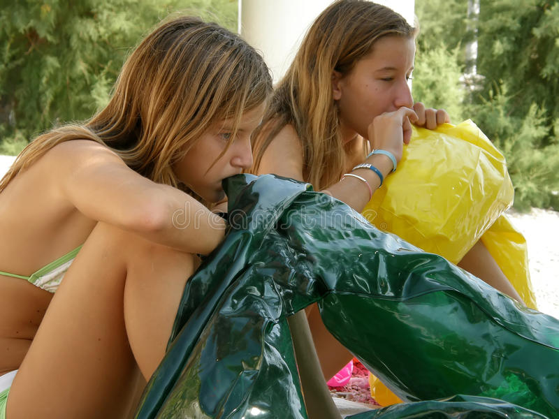 Sisters inflate beach toys royalty free stock image