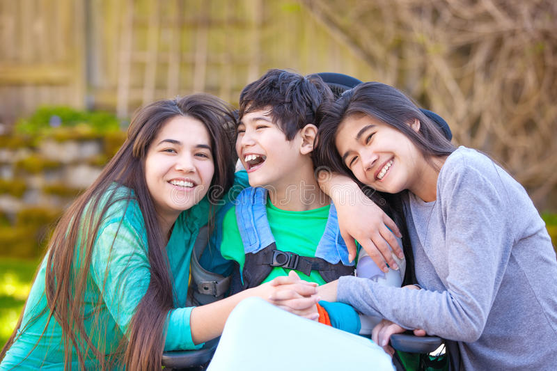 Sisters laughing and hugging disabled little brother in wheelchair outdoors royalty free stock photos