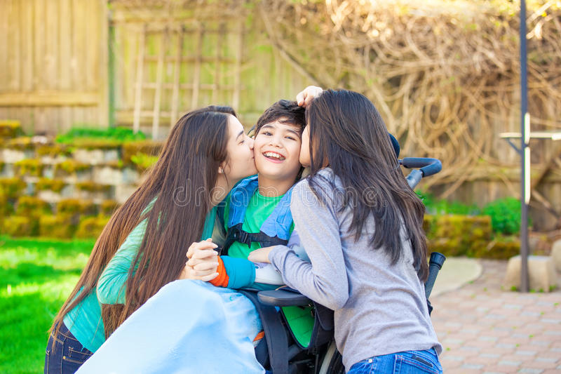 Sisters laughing and hugging disabled little brother in wheelchair outdoors royalty free stock image
