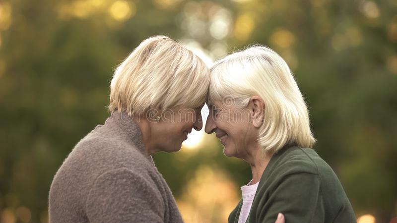 Sisters leaning heads outdoor, supporting to each other, warm family relations stock photography